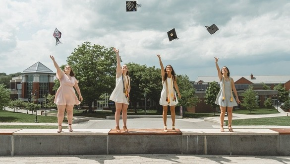 four college women graduates tossing caps